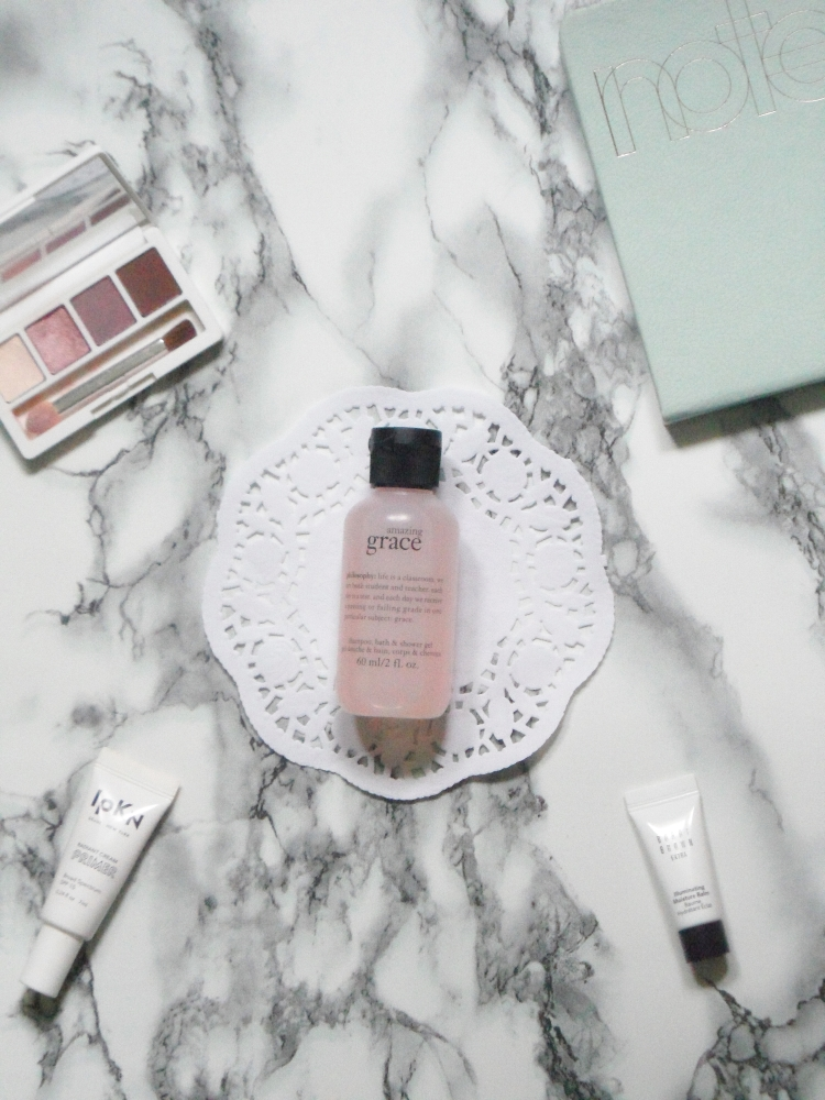 a bottle of shower gel, an eyeshadow palette, and two primers sitting on a marble counter
