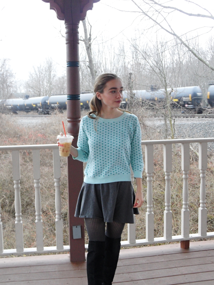 fashion blogger wears polka dot sweater and drinks coffee