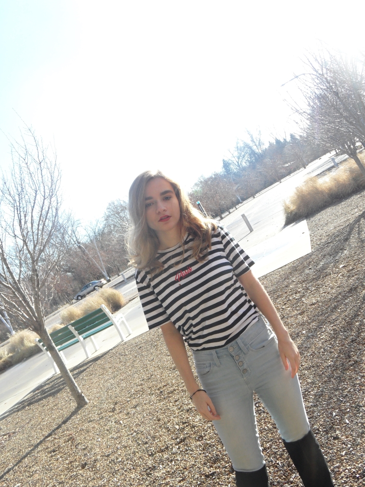 fashion blogger poses in striped top and jeans