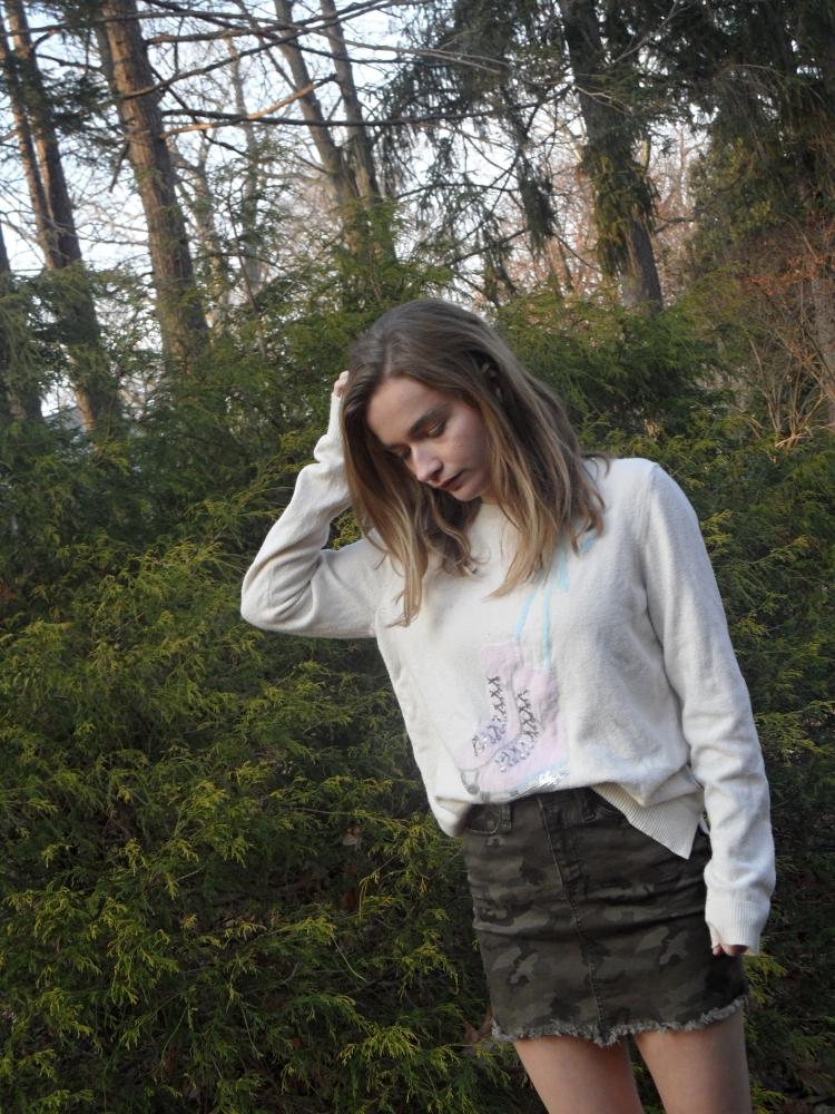 fashion blogger wears cream sweater and camo skirt