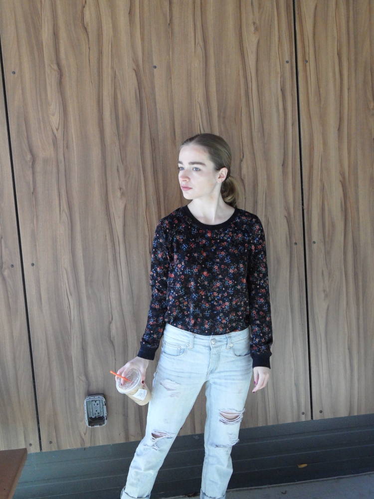 fashion blogger wears floral sweater, holds coffee