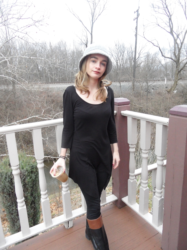 fashion blogger wears hat, holds coffee